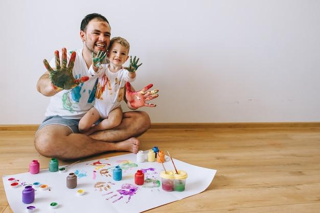 Padre y niño divirtiéndose pintando en casa