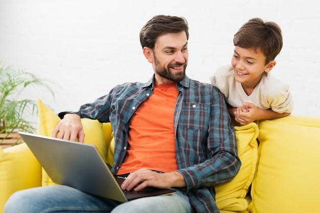 Padre y niño lindo mirando en la computadora portátil