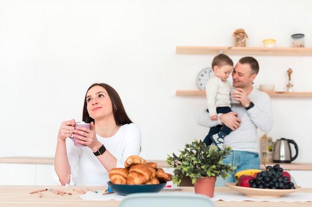 Padre con niño mientras la madre está en la mesa en la cocina