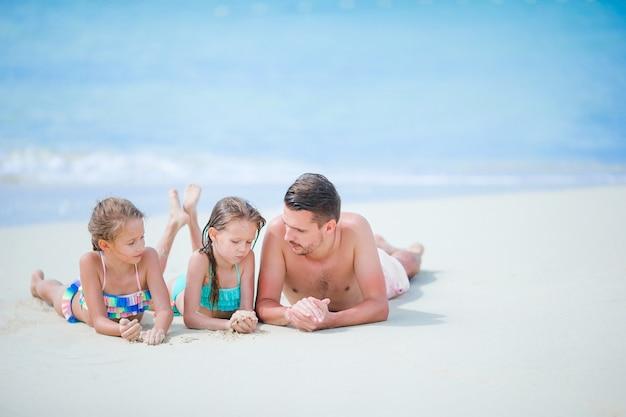 Padre y niños pequeños disfrutando de vacaciones en la playa