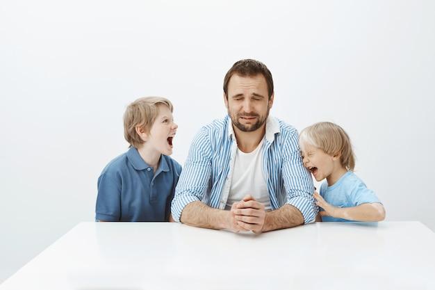 El padre no puede lidiar con hijos enérgicos con mal comportamiento. papá sentado a la mesa y llorando de sentimientos desesperados mientras los niños pequeños gritan y discuten