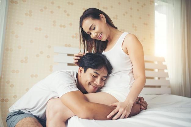 Padre oyendo a su hijo o hija pateando dentro de la madre en la cama en casa