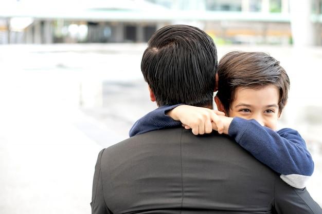 El padre, el padre soltero y el hijo llenan al hijo feliz abrazando en el distrito comercial urbano, la familia de la felicidad del padre y el hijo.