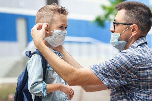 El padre pone una máscara de seguridad en la cara de su hijo. colegial caucásico con mochila. volver al concepto de escuela. nuevo normal