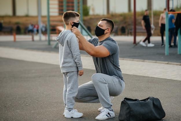 Un padre le pone una máscara a su hijo en el patio de recreo después de entrenar durante la puesta de sol.