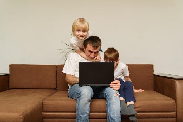 Padre con portátil sentado en el sofá con sus dos hijos. los niños llevaron a papá a descansar.