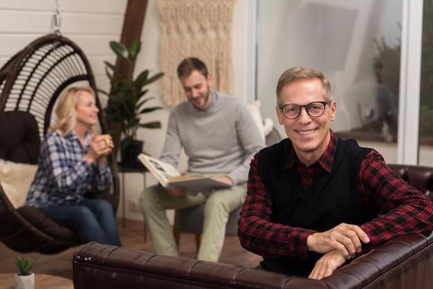 Padre posando mientras sonríe en el sofá con familia desenfocada