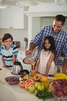 Padre prepara batido con sus hijos en la cocina