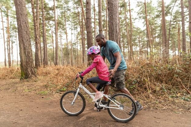 Padre preparando a su hijo para un paseo en bicicleta