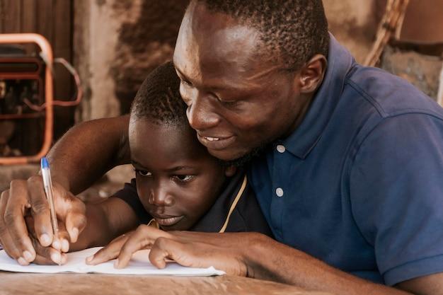 Padre de primer plano enseñando a niño a escribir