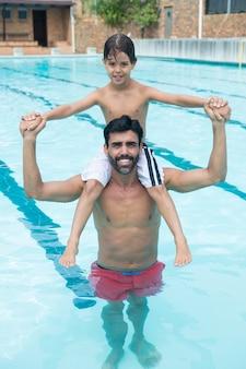 Padre, proceso de llevar, hijo, en, hombro, en, piscina