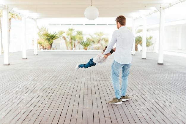 Padre que hace pivotar al niño por los brazos en primera línea de playa