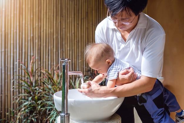 El padre que limpia las pequeñas manos asiáticas del bebé del niño del niño en fregadero y el agua caen del grifo