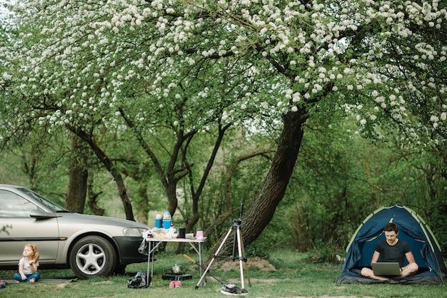 Padre que trabaja en línea en internet en un campamento con un niño. trabajo independiente. vacaciones familiares con un niño cerca de un coche y una tienda.
