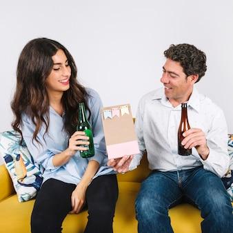 Padre recibiendo el regalo de la hija mientras bebe cerveza