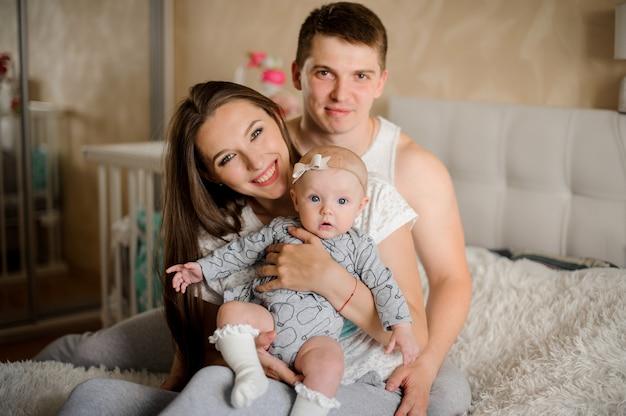 Padre sentado detrás de madre e hija pequeña en la habitación