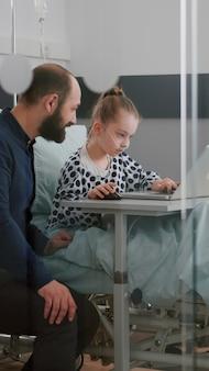 Padre sentado con su hija enferma en la sala del hospital mientras juega videojuegos de terapia en línea usando laptop