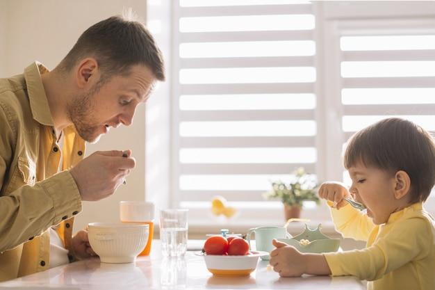 Padre soltero e hijo comiendo cereales