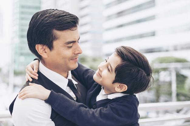 Padre soltero padre e hijo abrazando a su hijo en el distrito de negocios urbano