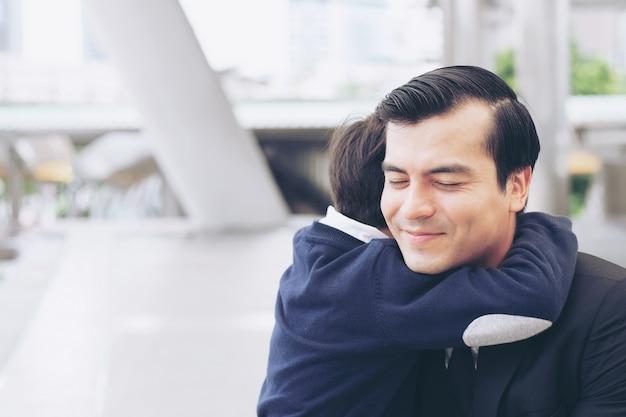 Padre soltero padre e hijo llenan feliz abrazando hijo en distrito de negocios urbano