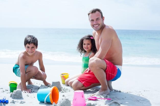 Padre sonriente jugando con hija e hijo en la playa
