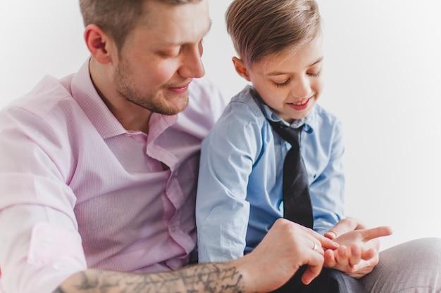 Padre sonriente jugando con la mano de su hijo
