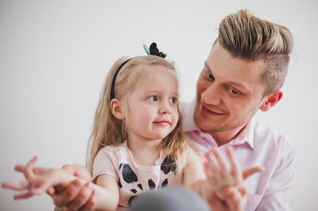 Padre sonriente jugando con las manos de su hija