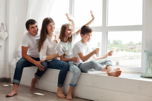 Padre sonriente que juega con sus niños que se sientan cerca de la ventana