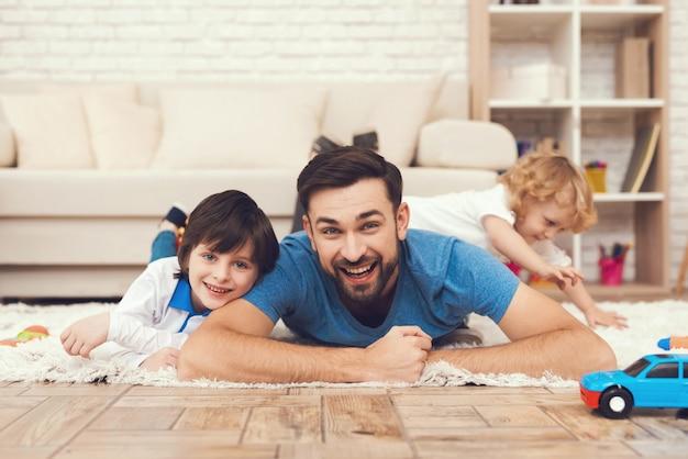 El padre de la sonrisa y los hijos felices juegan con los juguetes