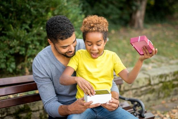 Padre sorprendiendo a su niña con un nuevo teléfono móvil