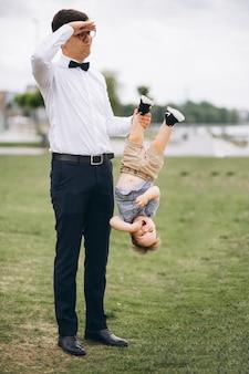 Padre sosteniendo a su hijo por la pierna