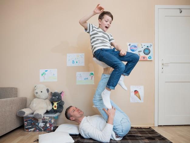 Padre sosteniendo al niño usando sus piernas