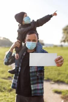 Padre sosteniendo un papel en blanco y sosteniendo a su hijo