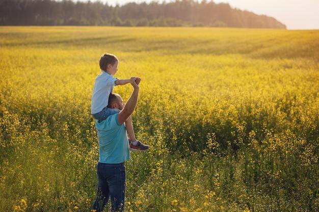 Padre sosteniendo a su hijo sobre los hombros y de pie
