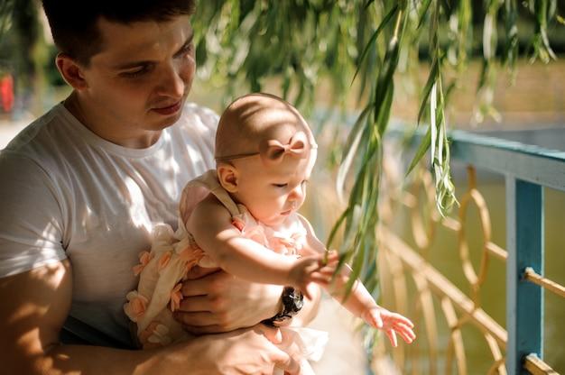 Padre sosteniendo a su pequeña hija en las manos entre las hojas del sauce