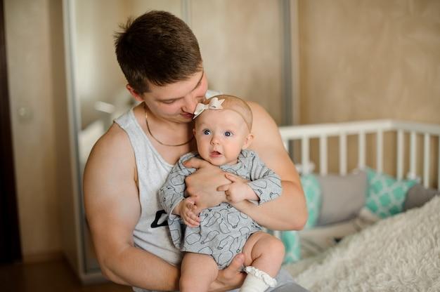 Padre sosteniendo a su pequeña hija de ojos azules en las manos