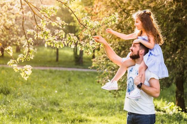 Padre con su hija en el hombro para tocar la rama de un árbol