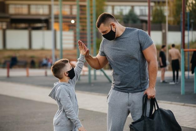Un padre y su hijo se paran en un campo de deportes con máscaras después del entrenamiento durante la puesta de sol.