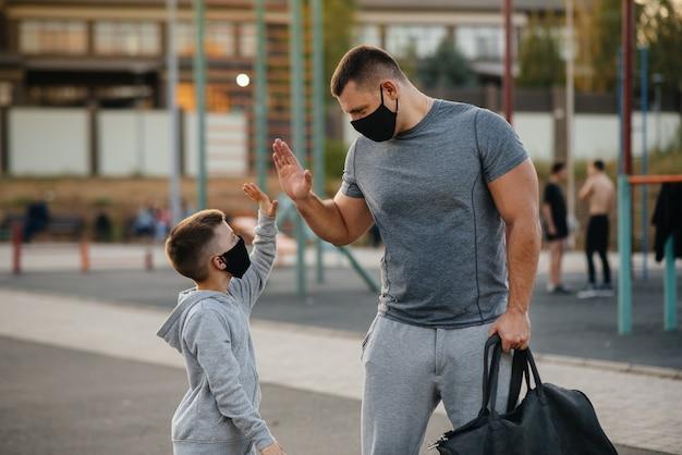 Un padre y su hijo se paran en un campo de deportes con máscaras después del entrenamiento durante la puesta de sol