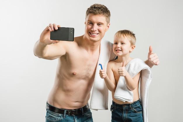 Padre y su hijo que muestran el pulgar arriba de la señal que toma autofoto en el teléfono móvil contra el fondo gris