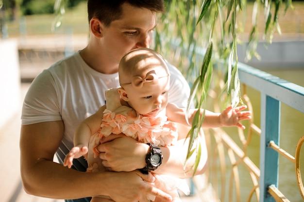 Padre con su pequeña hija en las manos entre el sauce