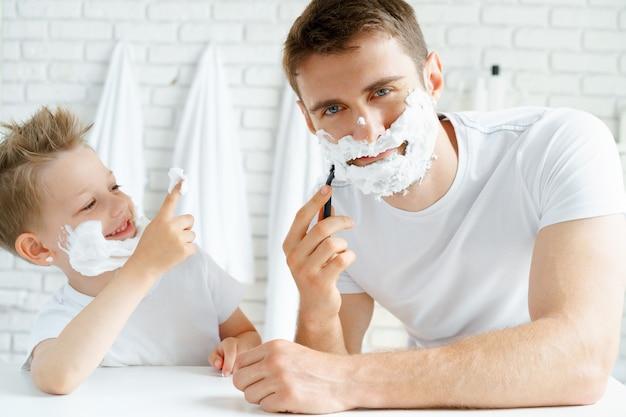 Padre y su pequeño hijo afeitándose juntos en el baño.