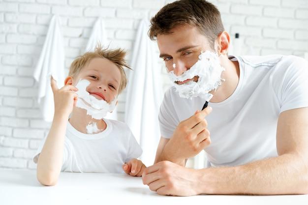 Padre y su pequeño hijo afeitándose juntos