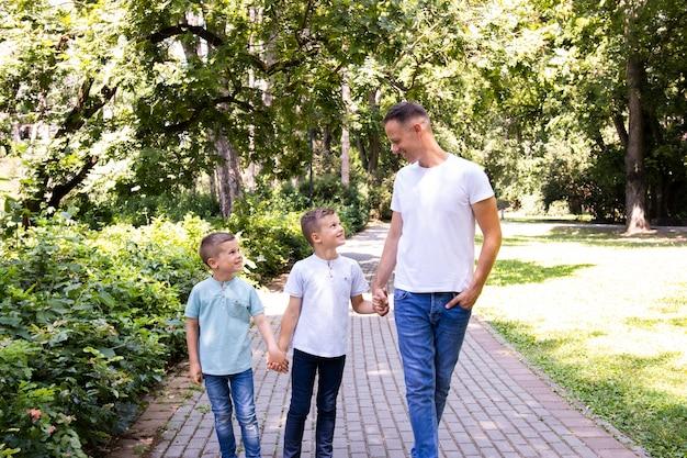 Padre con sus dos hijos en el parque.