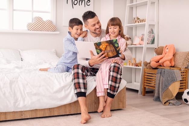 Padre y sus hijos pequeños leyendo un cuento antes de dormir en casa