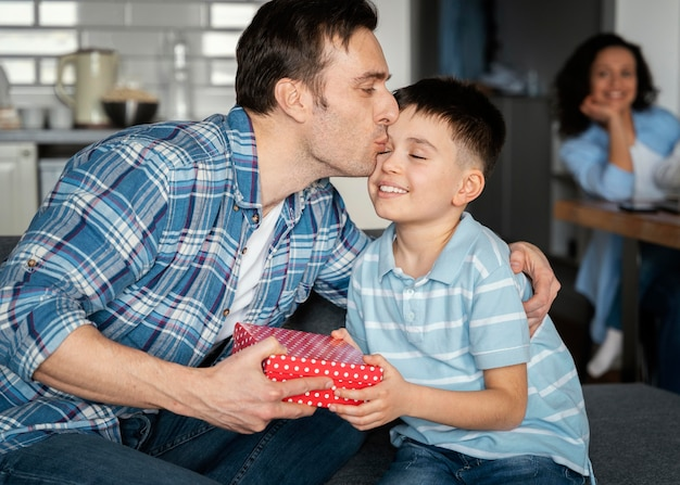 Padre de tiro medio besando a su hijo