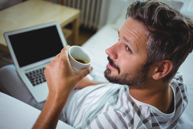 Padre usando laptop mientras tomando un café en la sala de estar