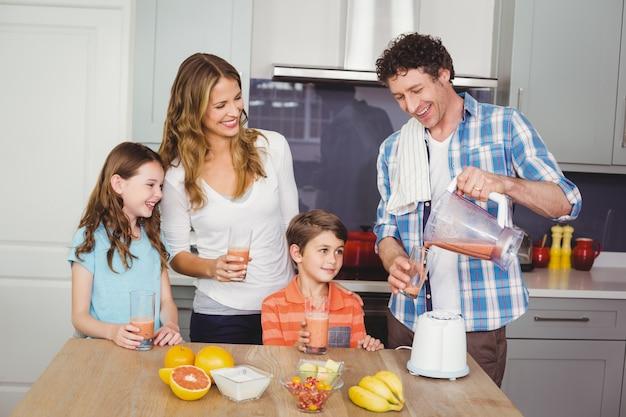 Padre vertiendo jugo de fruta en vaso con familia