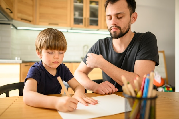 Padre viendo hijo dibujar
