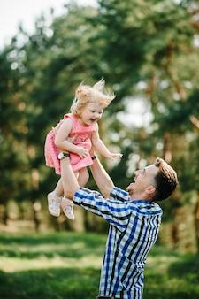El padre vomita y hace girar a la hija sobre la naturaleza en las vacaciones de verano. papá y niña jugando en el parque a la hora del atardecer. chica volando. concepto de familia amistosa. de cerca.